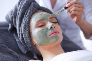 Woman getting facemask at a spa