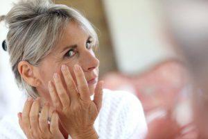 Grey-haired woman looking at her wrinkles
