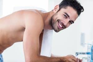 Man smiling washing his face