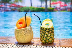 A pineapple and cantaloupe drink next to the pool