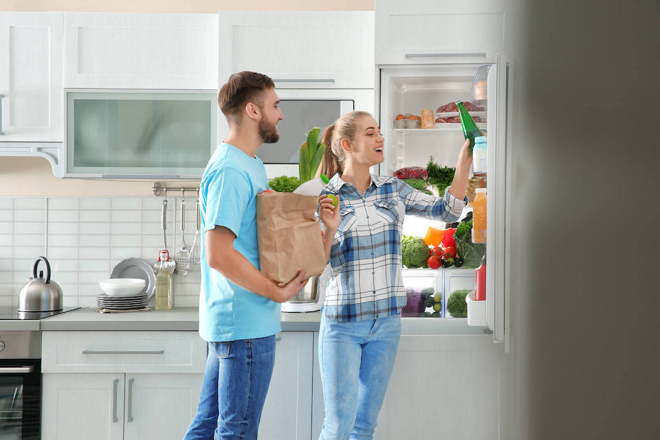 Man and woman putting groceries away in their fridge