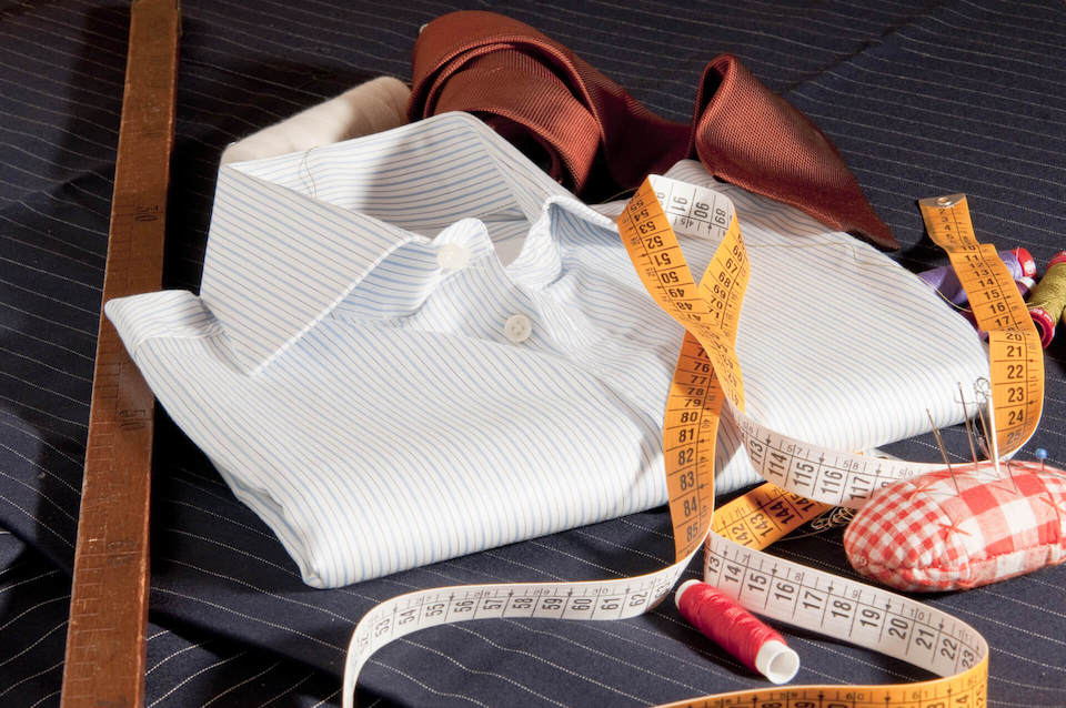 Folded up men's white dress shirt with a tape measure nearby