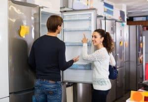Couple looking inside refrigerator