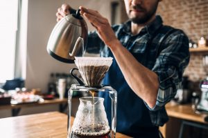 Man pouring hot water into coffee