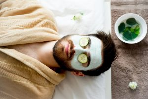 Man at the spa with cucumbers over eyes and face mask