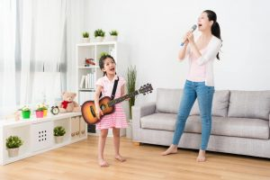 Young woman and kid singing karaoke at home