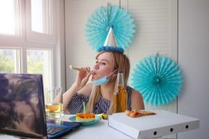 Woman blowing streaming for a virtual birthday party