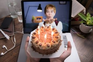Woman virtually blowing out birthday candles on a call