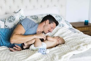 Dad looking at newborn on the bed