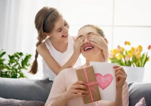 Child covering moms eyes holding a handmade card for Mother's Day gift
