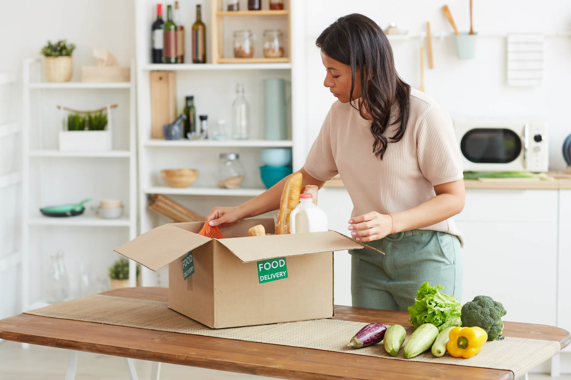 Woman opening her box of online groceries