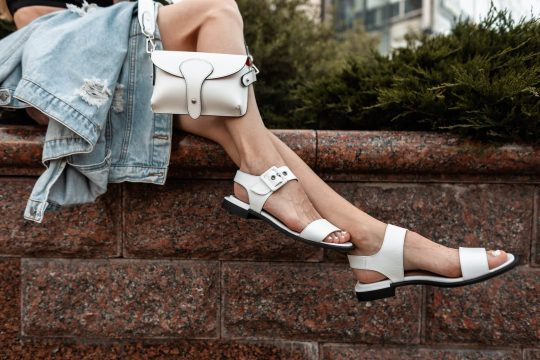 Woman with white sandals and white purse sitting on a retaining wall