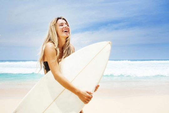 Woman smiling holding a surfboard on the beach