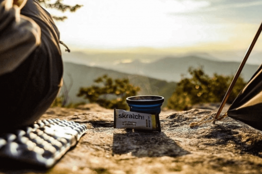 Woman with items from her Cairn subscription box overlooking a mountain view