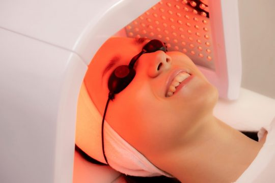 Woman putting her head into a red light therapy machine