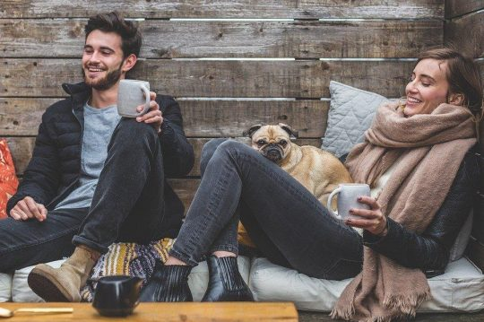 man and women on couch with pug