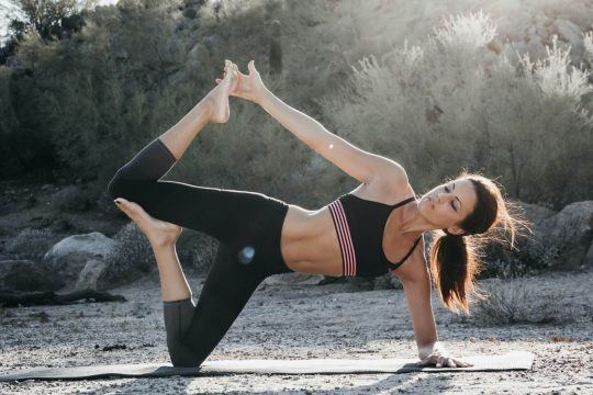 Woman stretching while wearing clothes from YogaClub