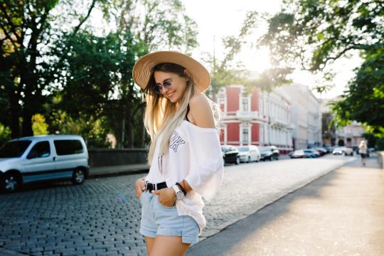 woman in the street with sun hat, shorts and white shirt