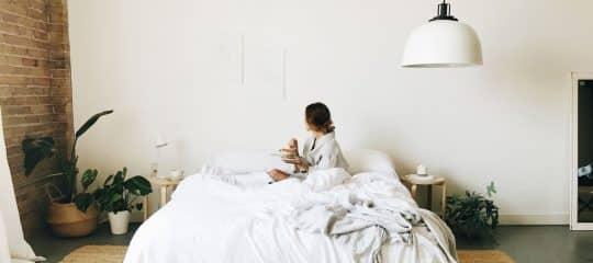Woman enjoying her silk comforter from Cozy Earth