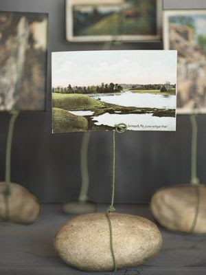 River rocks with wire around it, holding a postcard up