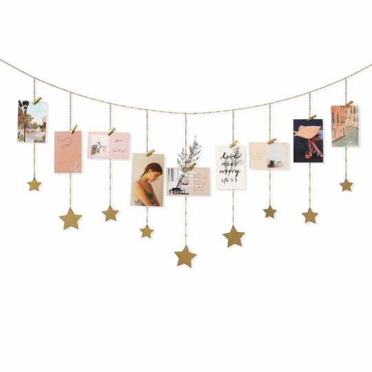 Postcards and stars hung up on a wall garland