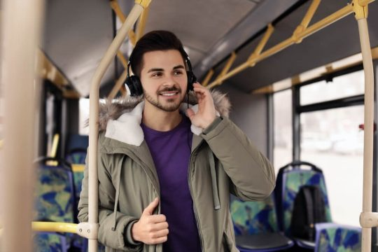 Young man listening to headphones on a bus