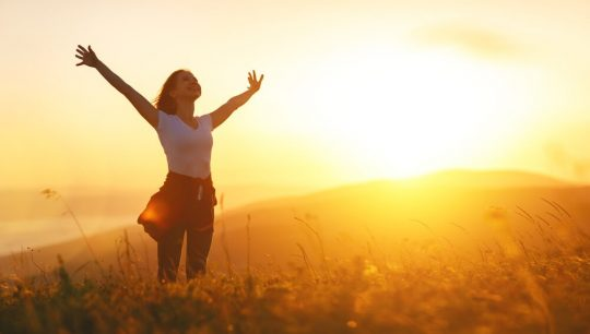 Woman standing in a sunny field with her arms stretched out