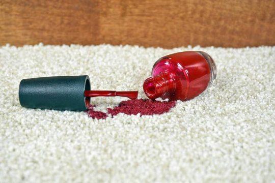 Red nail polish spilled on white carpet