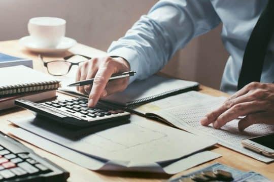 Man calculating his long term debt ratio
