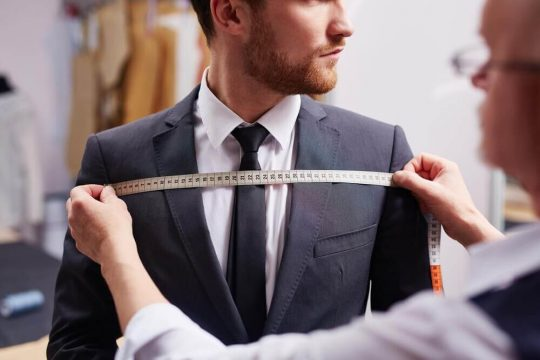 Man getting measured by a custom suit maker