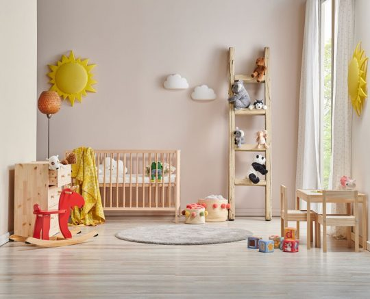 Adorable nursery with a peach wall, natural wood furniture and some stuffies and a red rocking horse