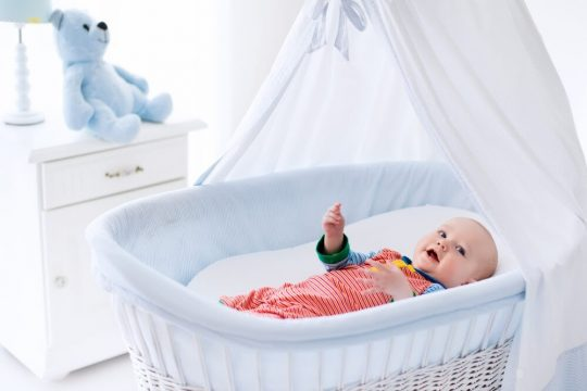 Baby boy laying in a bassinet, smiling at something in the distance