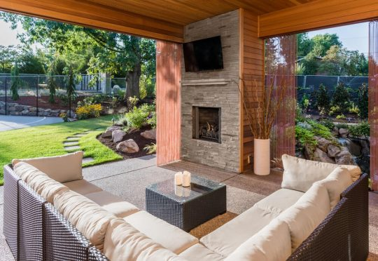 Outdoor living space with sectional couch, fireplace and outdoor tv mounted on a side wall
