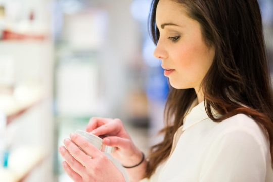 Woman looking at a skincare product in the store