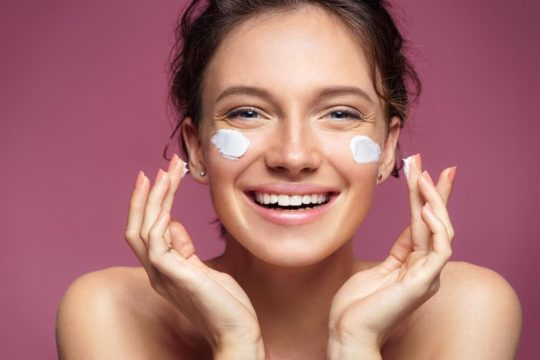 Happy woman with skincare cream on her cheeks