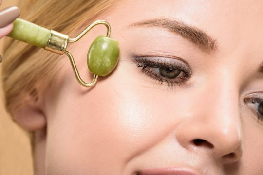 Woman using a jade roller on her cheeks