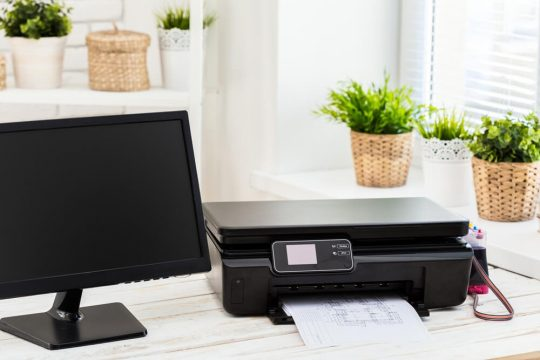 Black monitor and a black all-in-one printer; just two of the home office essentials