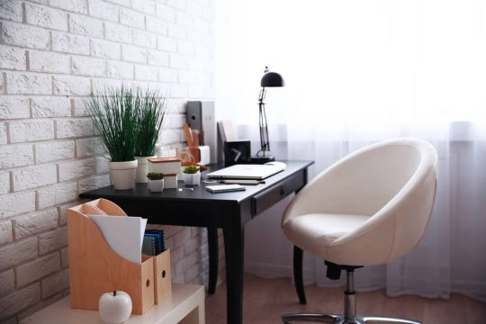 Bllack desk with a modern white chair  in front of a white brick wall and some warm accents