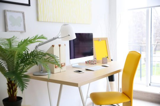 Modern desk setup with a yellow accent chair, green house plant and yellow wall art & desk memo pad