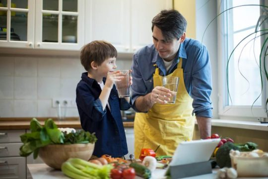 Man and son drinking water to reduce bloating and feel hydrated