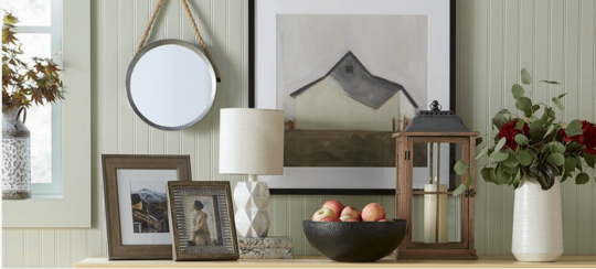 Tabletop with picture frames, a lantern and a bowl of apples