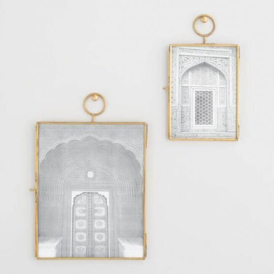 Two gold-rimmed pictures hanging on the wall