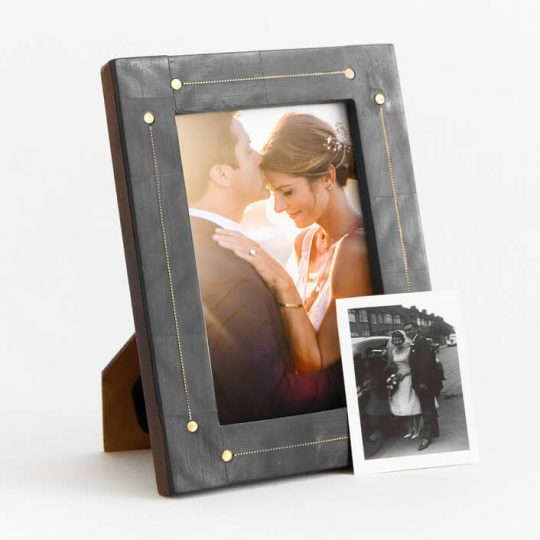 Wedding photo in a black, distressed frame with a picture of grandparents on their wedding day in front