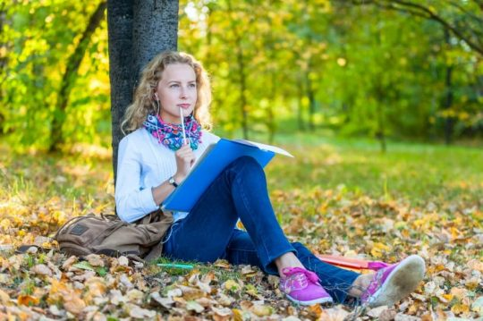 Woman sitting by a tree thinking as she writes in her journal