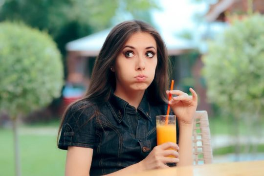 Woman looking concerned as she drinks an orange smoothie and thinks about something