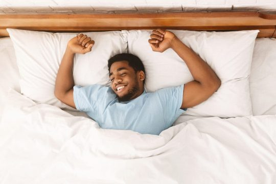 Man stretching in bed, smiling after having a dream