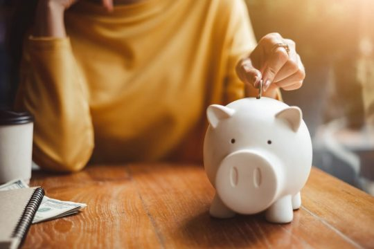 Woman putting change in a piggy bank