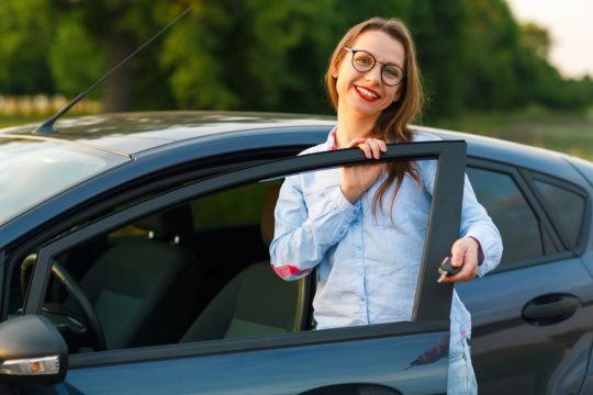 Woman smiling with her new, pre-owned car