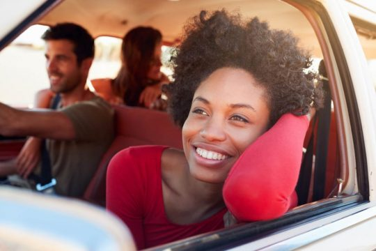 Woman looking out the window, smiling during a road trip