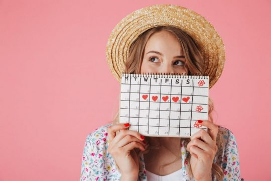 Woman holding up a calendar that tracks her cycle